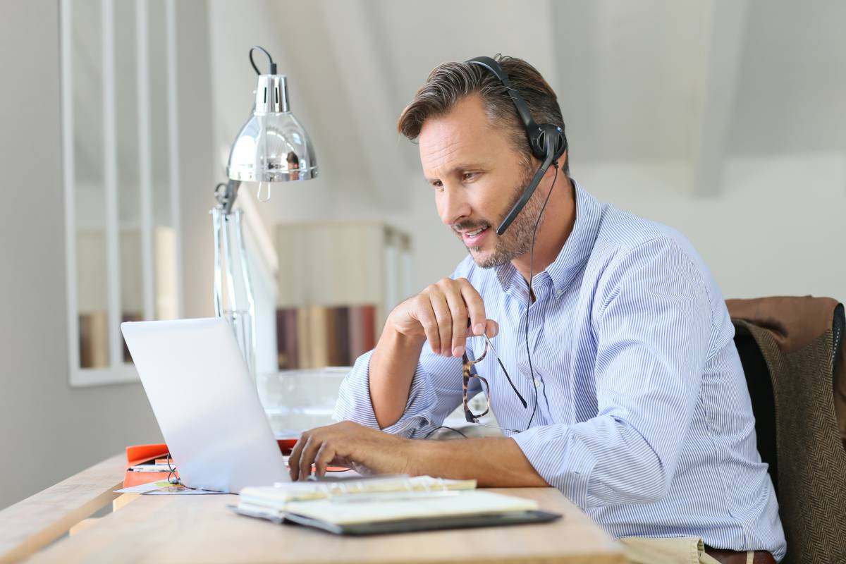A man working from home using a laptop and a headset and providing great customer service