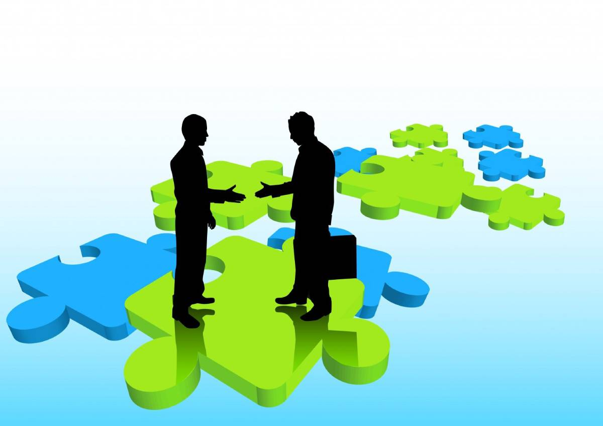 Image of 2 business people extending hands on green and blue puzzle pieces.