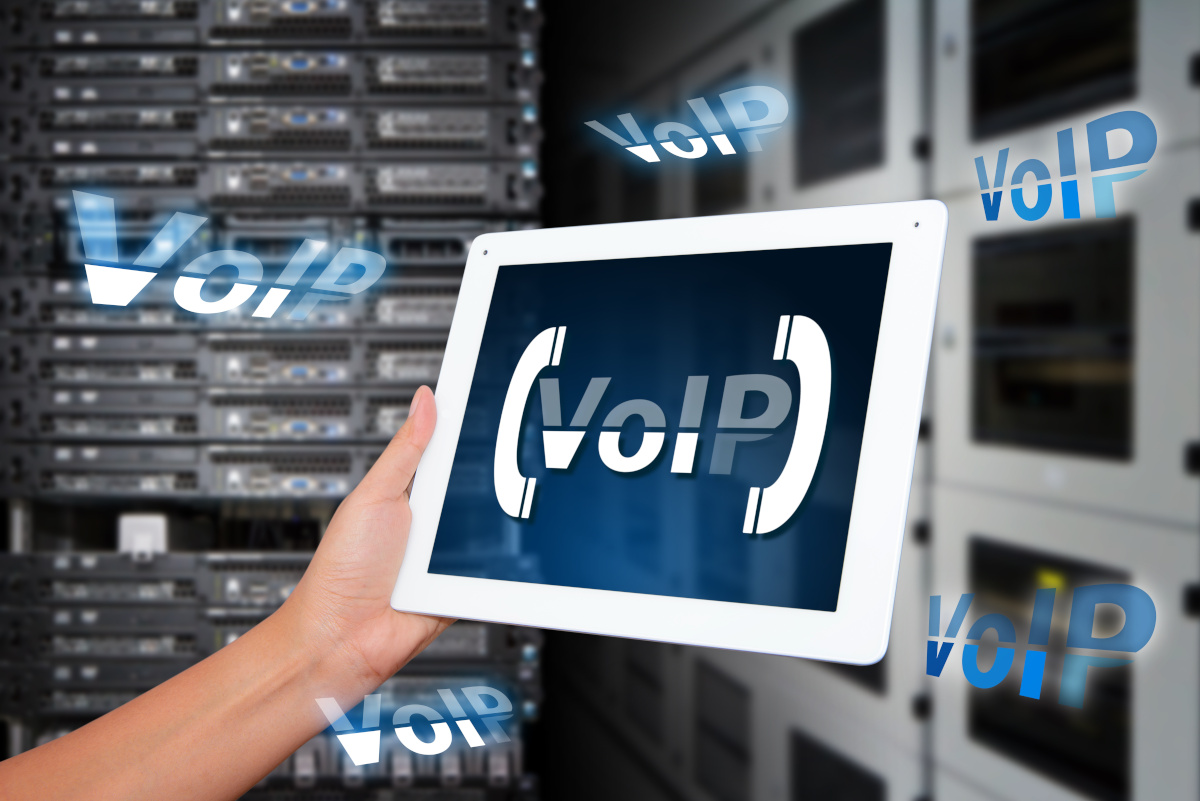 Hand Holding Tablet with VoIP Lettering on Server Room Background