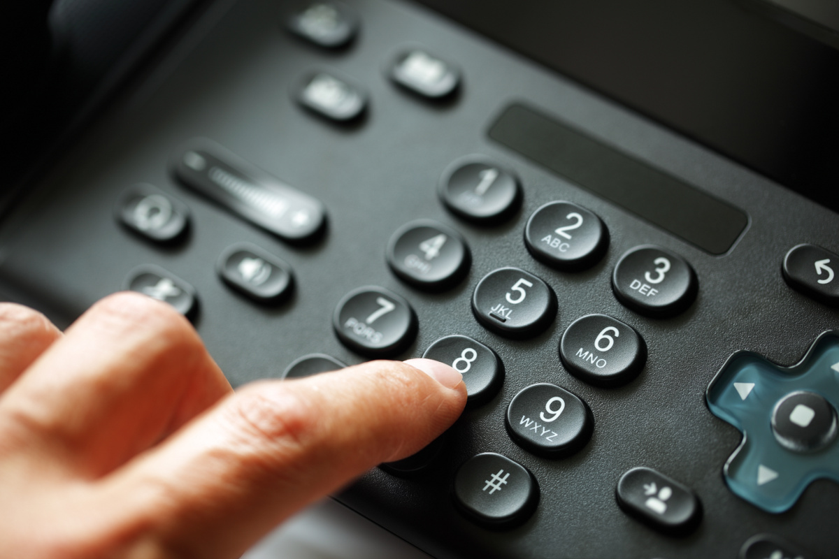 Close Up of Finger Dialing the Number 8 on a VoIP Phone